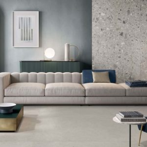 A modern sofa in a room tiled with the Silver Grain collection tile by Italgraniti